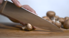 Mushrooms being sliced on a cutting board in slow motion Stock Footage