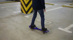 Legs of boy riding on waveboard in underground parking Stock Footage