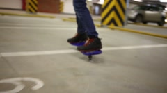 Closeup of teen feet riding on waveboard in underground parking Stock Footage