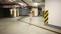 Boy and girl play water fight in big underground parking Stock Footage