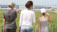 Back of woman and two children standing near fence of airport Stock Footage