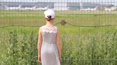 Back of girl standing near lattice of airport and pointing Stock Footage
