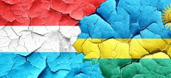 Luxembourg flag with rwanda flag on a grunge cracked wall Stock Illustration