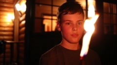 Closeup portrait of boy holding and shaking burning stick at night Stock Footage