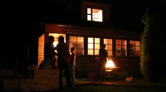 Talking unidentified people near house and brazier at summer night Stock Footage