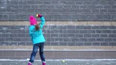 Girl throws yellow tennis ball near brick wall outdoor Stock Footage