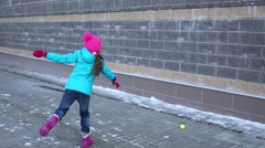 Girl throws and catches tennis ball near brick wall outdoor Stock Footage