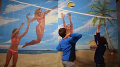 Woman, boy and girl play volleyball on beach in optical illusions Museum Stock Footage