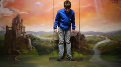 Boy stands on swing in optical illusions Museum at VDNKh Stock Footage