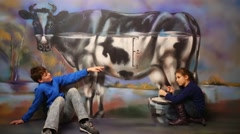 Boy strokes and girl milks cow in optical illusions Museum at VDNKh Stock Footage