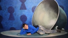 Boy lies near big cup in optical illusions Museum at VDNKh Stock Footage