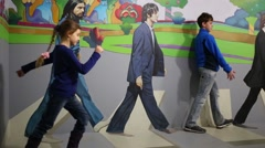 Boy poses with Beatles and girl goes in optical illusions Museum Stock Footage