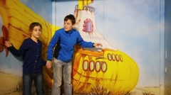 Girl and boy stand near yellow submarine in optical illusions Museum Stock Footage
