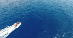 AERIAL: motorboat goes across blue sea surface with white trail Stock Footage