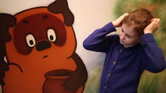 Girl scratching her head close to Russian Winnie Pooh Stock Footage