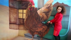 Woman fills gasoline hen in optical illusions Museum at VDNKh Stock Footage