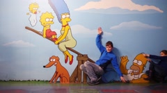 Boy and girl poses with Simpsons in optical illusions Museum Stock Footage