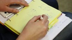 Hands of woman drawing dress in notebook on her laps Stock Footage