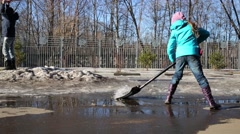 Girl and boy with big shovels clean dirt and last year snow Stock Footage