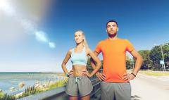 happy couple exercising at summer seaside - stock photo