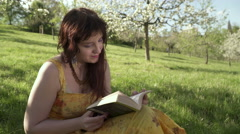A woman reading a book in the Petrin park in Prague Stock Footage