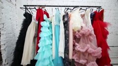 Bright dresses and coctumes hang on hanger in wardrobe Stock Footage