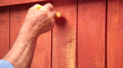 Close up of man's hands painting wooden fence with brown paint Stock Footage