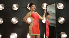 Pretty girl in red dress poses near mirror in room with lamps Stock Footage