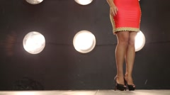 Beautiful girl in red dress stands near wall with lamps in studio Stock Footage