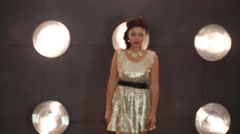 Beautiful girl in shiny dress goes near wall with lamps in studio Stock Footage