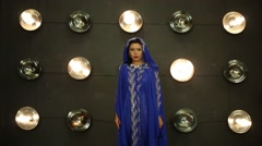 Woman in blue mantle poses near wall with lamps in studio Stock Footage