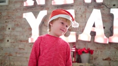 Little cute boy in santa cap poses in studio with big letters New Year Stock Footage