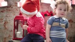 Two children in santa caps laugh on big trunk in studio Stock Footage