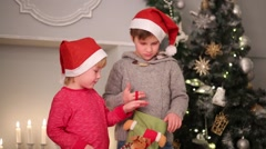 Two boys in santa caps take out sock gift near christmas tree Stock Footage