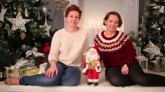 Two women sit on floor with little santa claus near christmas tree Stock Footage