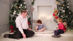 Father with two children sit on floor and play with model railway near christmas Stock Footage