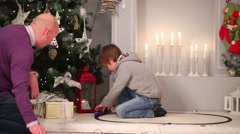 Father with his son play with model railway near christmas tree Stock Footage