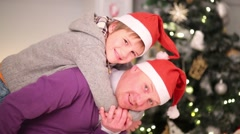 Father with son in santa caps pose near christmas tree Stock Footage