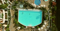 AERIAL: pool in hotel with people swimming in it. - stock footage