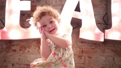 Little girl smiles and sits near wall with big letters Stock Footage