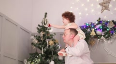 Father with daughter on his shoulders hang ball on christmass tree Stock Footage