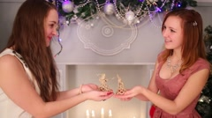 Two girls teenagers hold christmas toys near illuminated tree Stock Footage