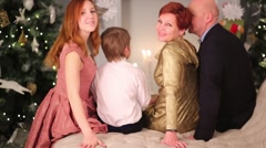Mother, father, son and daughter sit on couch and turn heads Stock Footage