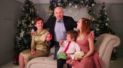 Mother, father, son and daughter pose on couch during christmas Stock Footage
