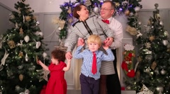 Mother, father, son and daughter pose near christmas trees Stock Footage