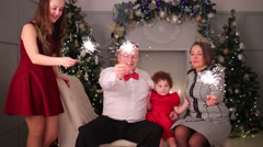 Mother, father and two daughters pose with sparklers during christmas Stock Footage