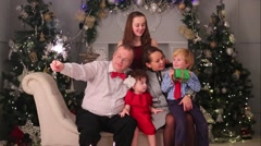 Mother, father, son and two daughters pose with sparklers and gift Stock Footage