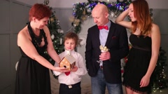 Mother, father, son and daughter pose with gingerbread house Stock Footage