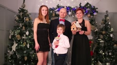Mother, father, son and daughter stand with gingerbread house Stock Footage