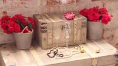 Beads in wine glasses and red flowers in pots on wooden chest Stock Footage